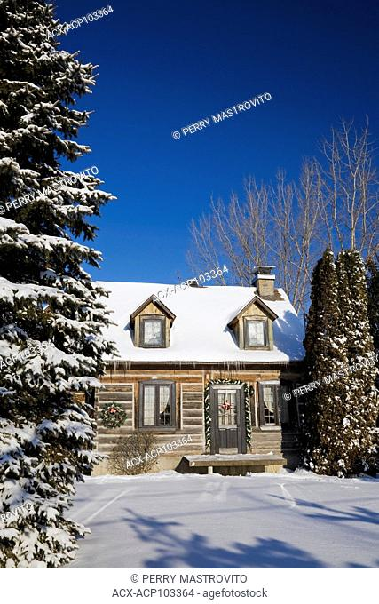 Residential cottage style reconstructed (1982) log home in winter with Christmas decorations, Quebec, Canada. This image is property released for calendar, book