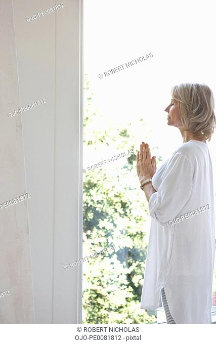 Older woman with hands folded in prayer