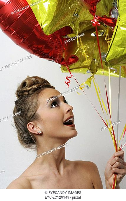 Portrait of happy young woman holding balloons, studio shot