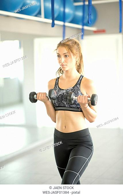Woman training biceps in gym