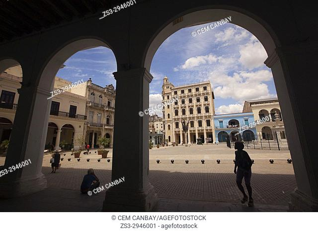 Framed view to the silhouettes of people and to Plaza Vieja Square with colorful buildings and art galleries at the background, Havana, La Habana, Cuba