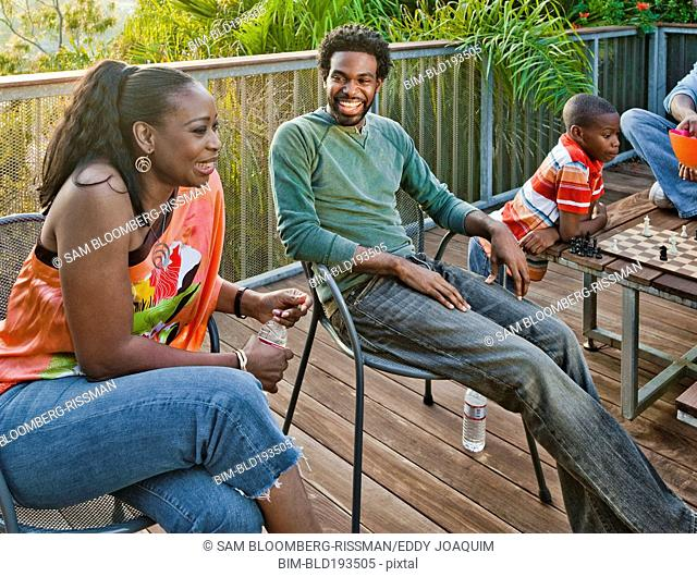 Black family relaxing on patio