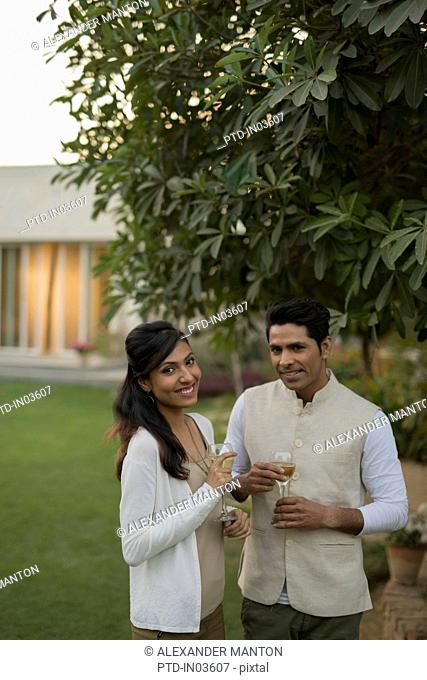 Man and woman standing outside home with glass of wine