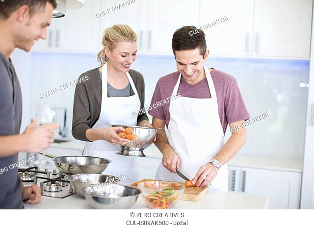 Mid adult man chopping carrots whilst friends watch in kitchen