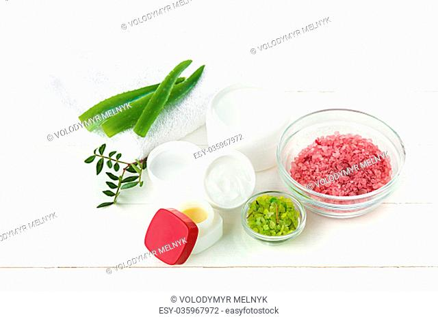 Spa concept with salt, mint, lotion, towel on white wooden background