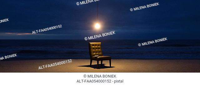 Light bulb illuminated over chair on beach at night