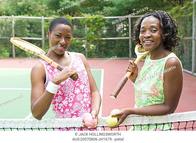 Portrait of two mid adult women holding tennis rackets and smiling in a court