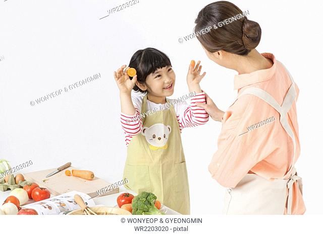Young girl playing with carrot slices and her mother looking at her both in apron and enjoying cooking together