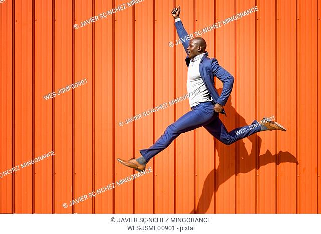 Businessman jumping in the air in front of orange wall