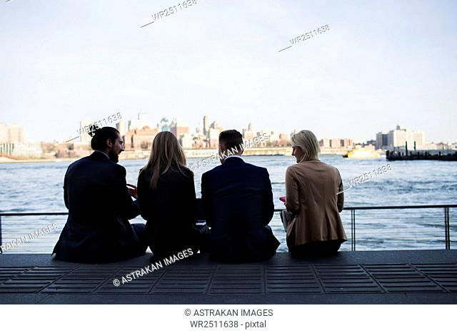 Rear view of business colleagues sitting on promenade by sea against clear sky