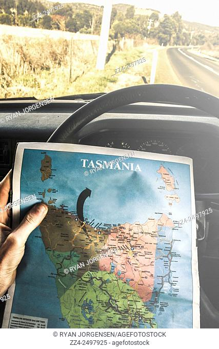 Car interior shot on the hands of a travelling tourist holding map of Tasmania by steering wheel while routing the places and destinations to tour