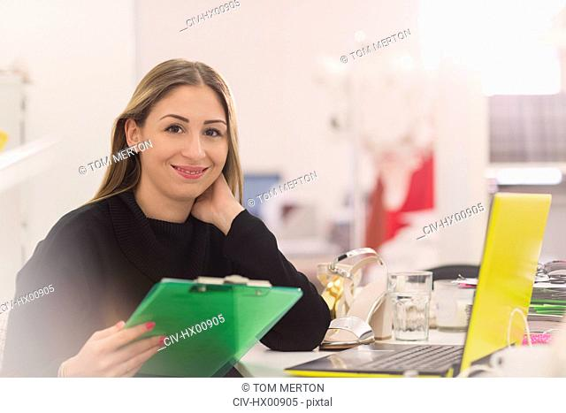 Portrait smiling fashion buyer with clipboard working at laptop in office