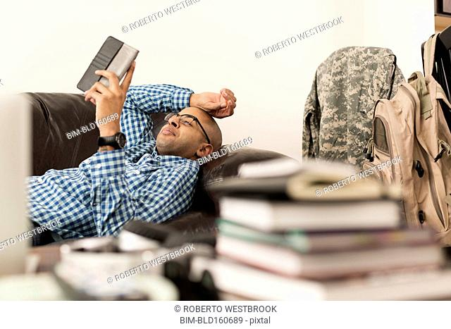 Mixed race man using digital tablet on sofa near books