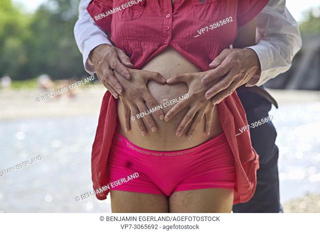 Couple, pregnancy, close-up of belly, shape of heart, love. At river Isar, Munich, Germany