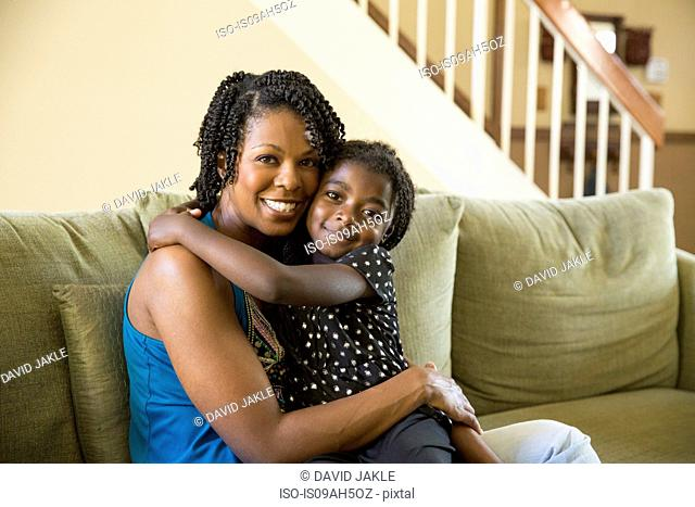 Portrait of mature woman and daughter sitting on sofa