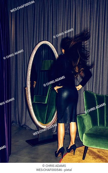 Young woman standing in front of a mirror tossing her hair