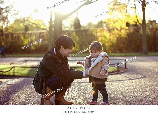 A mother putting her daughter's coat on in the park