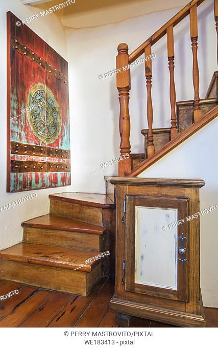 Pinewood staircase leading to upstairs floor inside an old 1820 cottage style fieldstone house with stacked log extension, Quebec, Canada