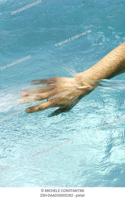 Man splashing in pool, cropped view of hand