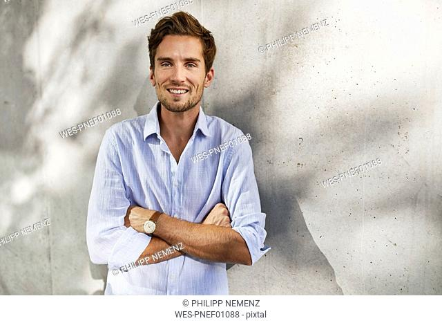 Portrait of smiling young man in front of concrete wall