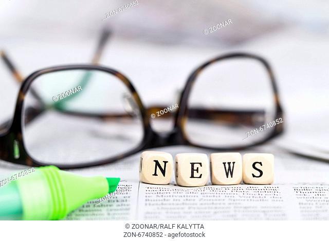 Holzbuchstaben mit dem Wort News mit Tageszeitungen, Textmarker und Brille