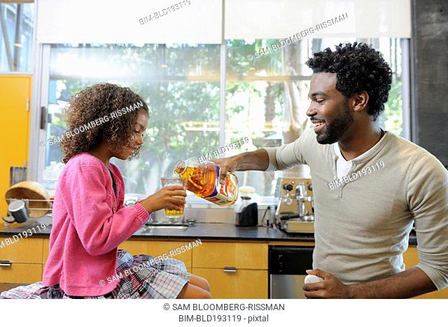 Father pouring juice for daughter
