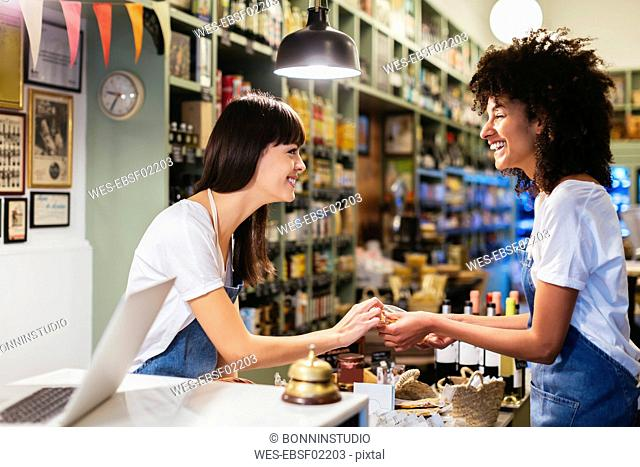 Two happy women at the counter in a store