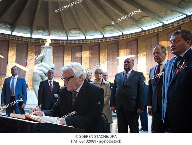 German Foreign Minster Frank-Walter Steinmeier (C) signs the guestbook of the Mamayev Kurgan memorial complex that commemorates the Battle of Stalingrad during...