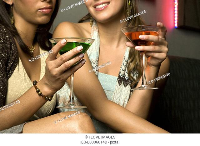 Two young women drinking cocktails