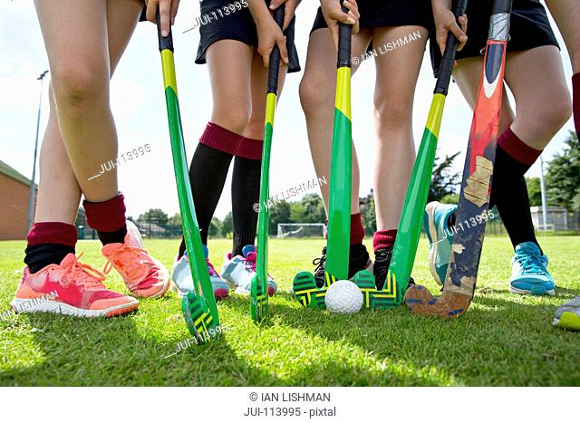 Legs of middle schoolgirls playing field hockey in physical education class