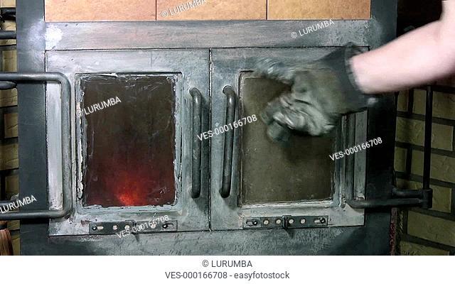 Frau wirft Holz in den Ofen, um das Feuer anzuheizen