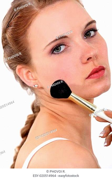 young woman putting make up on her face