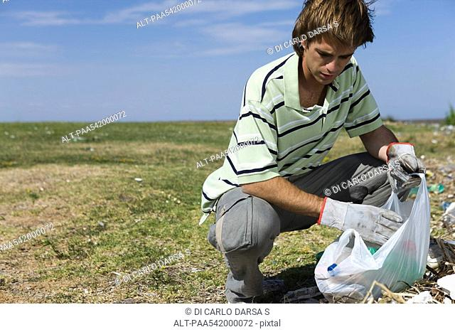 Male picking up trash in field