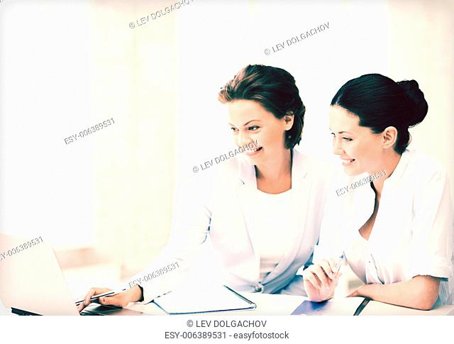 picture of two businesswomen working with laptop in office