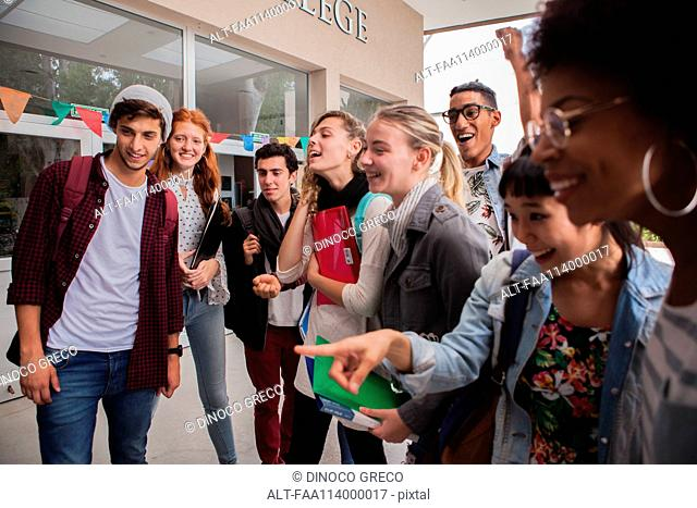 College students gathered together on campus, looking excited