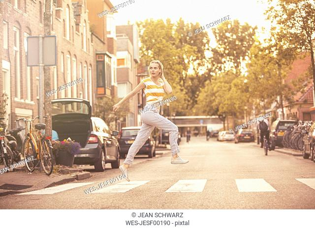Young woman jumping in the air on zebra crossing