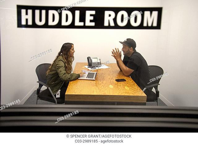 """Casually dressed young adult employees at the Vans Shoe Company corporate headquarters in Costa Mesa, CA, confer one on one in a """"""""huddle room"""