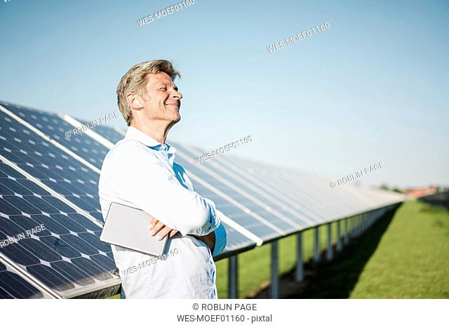 Businessman with wireless earphone using tablet at solar park