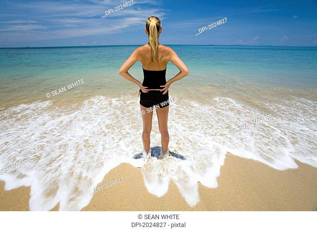 a woman stands in the shallow clear waters of a tropical island, koh lanta krabi province thailand