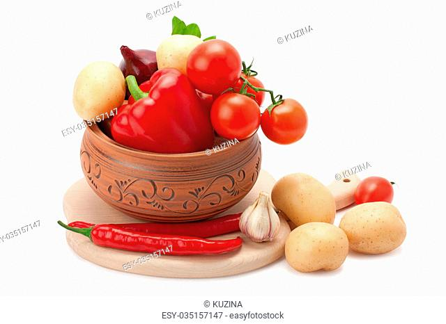 vegetables stacked in a clay pot isolated on white background