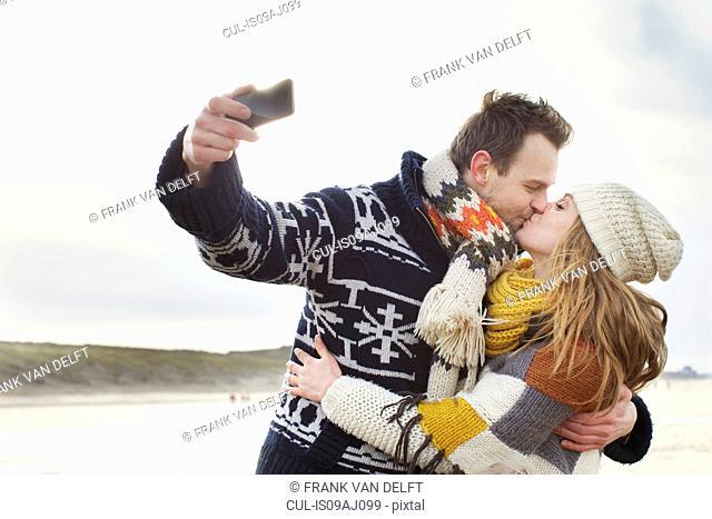 Mid adult couple taking self portrait with smartphone on beach, Bloemendaal aan Zee, Netherlands