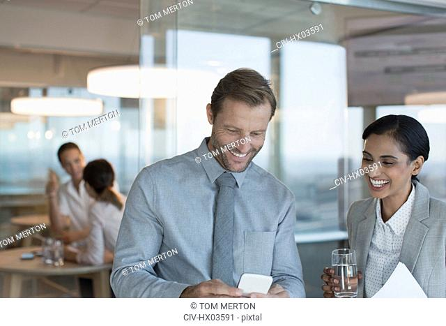 Businessman and businesswoman using cell phone in office