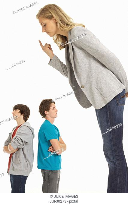 Mother towering over in authority over teenage boys