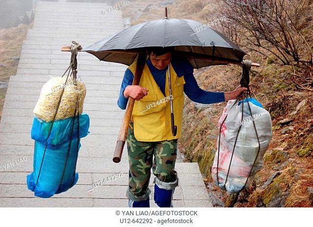 A man is cary food up to the mountain of Huang - shan.It will take him up to 9 hours.Those mountains are also called yellow mountains by the chinese people