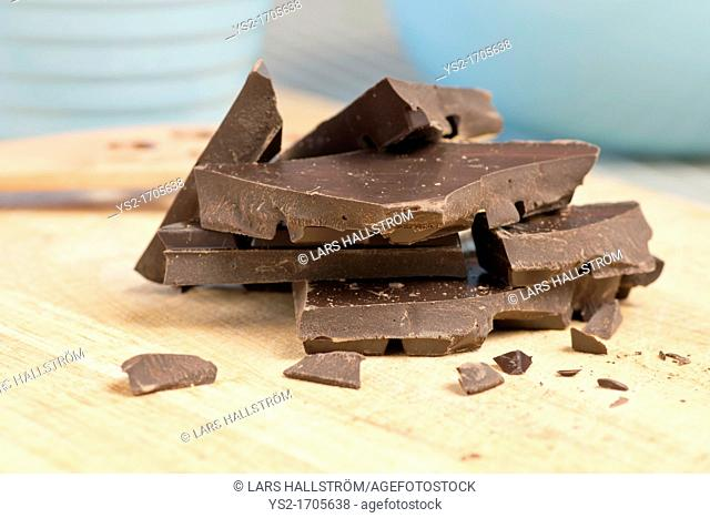Pieces of broken dark chocolate stacked on a cutting board