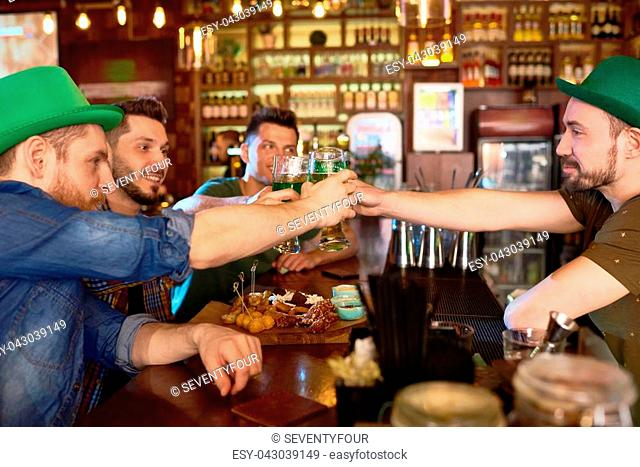 Three young friends and bearded barman clinking beer glasses together while sitting at counter and celebrating St. Patricks Day