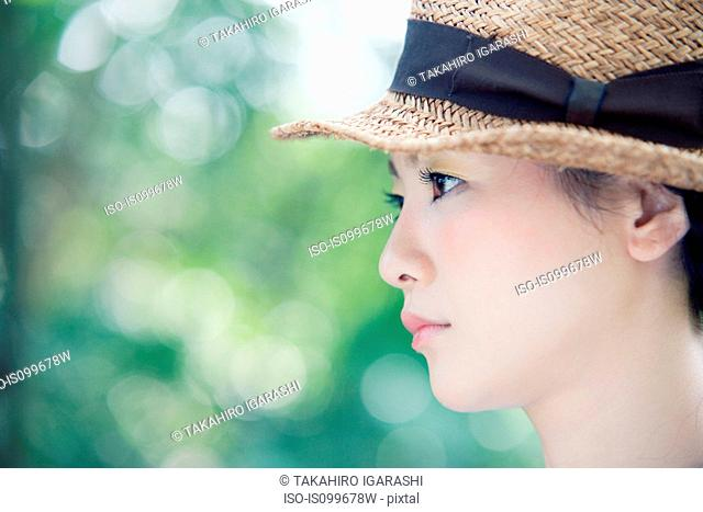 Young woman wearing straw hat, portrait
