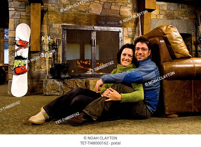 Man and woman hanging out in front of fireplace