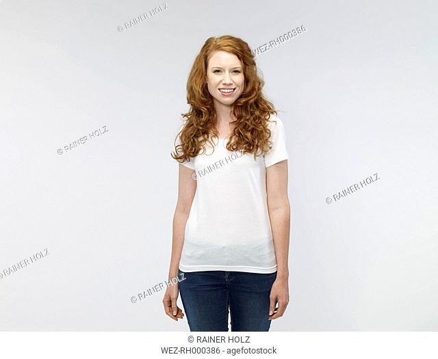 Portrait of smiling young woman in front of white background