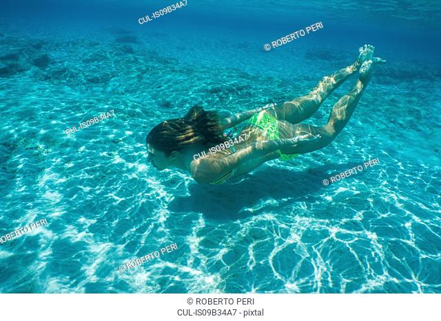 Underwater view of woman swimming in sea